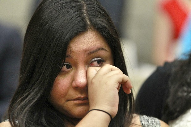 Myrna Orozco, 22, of Kansas City, Mo., an illegal immigrant originally from Mexico, wipes away tears while watching President Barack Obama announce Friday in Washington that the U.S. government will stop deporting and begin granting work permits to younger illegal immigrants who came to the U.S. as children and have since led law-abiding lives.