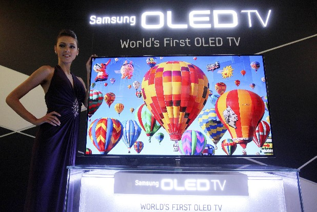 In this May 10, 2012 photo, a model poses with a 55-inch Samsung OLED, organic light-emitting diode, TV during a press conference in Seoul, South Korea. South Korean TV manufacturers are making billion dollar bets on a new display technology that promises an even thinner screen and imagery of eye-popping clarity. (AP Photo/Ahn Young-joon)