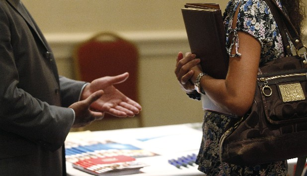 A prospective employer, left, speaks with a prospective employee during a jobs fair  in Oak Brook, Ill. A measure of future U.S. economic activity rose in May to the highest level in four years, a sign the economy will keep growing but at a modest pace. The Conference Board said Thursday that its index of leading economic indicators rose 0.3 percent last month, after a 0.1 percent drop in April.