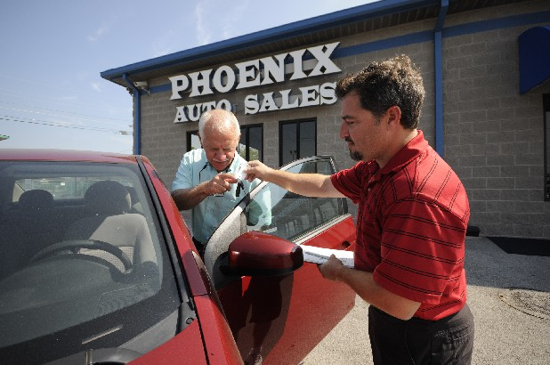 Steve Smith, left,  and his son, Derek, sell cars under the name of Phoenix Auto Sales on East 20th Street next to the Mountain View family of dealerships. Smith has been known for years as Big-Hearted Smitty.