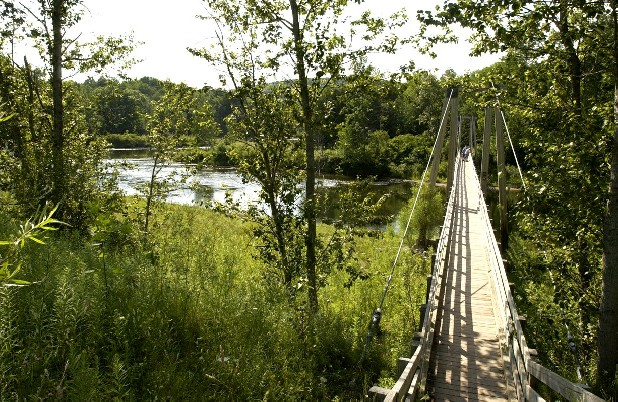 This July 27, 2003, file photo, shows a suspension bridge over the Manistee River southeast of Mesick, Mich., where the North Country Scenic Trail follows the river for miles. The North Country National Scenic Trail runs 4,600 miles from North Dakota to New York's eastern border. From there, it's about 40 miles across Vermont fields and mountains to the Appalachian Trail. Closing the 40-mile gap is a priority for the Michigan-based North Country Trail Association, the group responsible for the trail. (AP Photo/John L. Russell, File)
