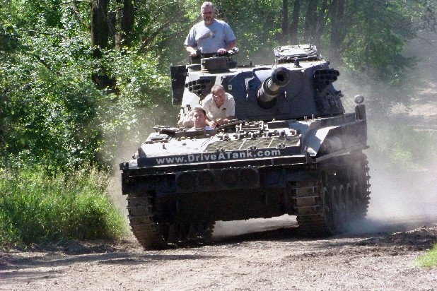 In this photo made June 9, 2012, Nick Walker of Amboy, Indiana drives a tank in Kasota, Minn., while his father Brad Walker looks out from the turret and Drive A Tank owner Tony Borglum sits behind him. For a fee, Drive A Tank gives people a chance to drive a tank around a mile-long dirt course and to crush a car with a tank. (AP Photo/Jeff Baenen)