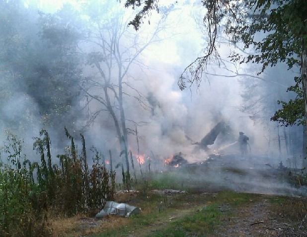 A firefighter hoses a burning aircraft in Whitfield County, Ga., on Saturday. The pilot, Chattanooga businessman Donald Holbrook, died when his Piper PA-31 Navajo crashed soon after takeoff from Dalton Municipal Airport.
