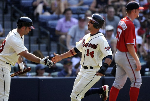 Atlanta Braves' Martin Prado (14) greets teammate Dan Uggla as he scores in front of Washington Nationals pitcher Stephen Strasburg in the third inning of their baseball game on Saturday, June 30, 2012, at Turner Field in Atlanta.