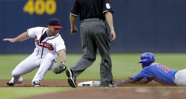 Chicago Cubs' Alfonso Soriano, right, dives to beat the throw to Atlanta Braves second baseman Dan Uggla after hitting a double int he first inning of a baseball game Wednesday, July 4, 2012, in Atlanta.
