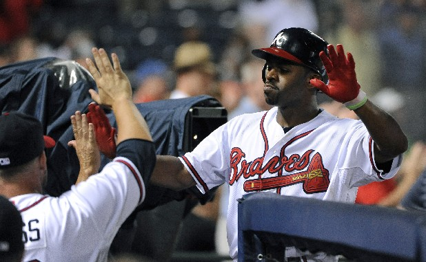 Atlanta Braves' Michael Bourn is greeted in the dugout after he scored during the sixth inning of a baseball game against the Chicago Cubs on Tuesday, July 3, 2012, at Turner Field in Atlanta.