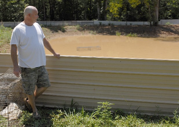 Turtle farmer David Driver looks over his turtle pond on Wednesday in Summerville, Ga. Driver says he is one of three turtle farmers in the state.