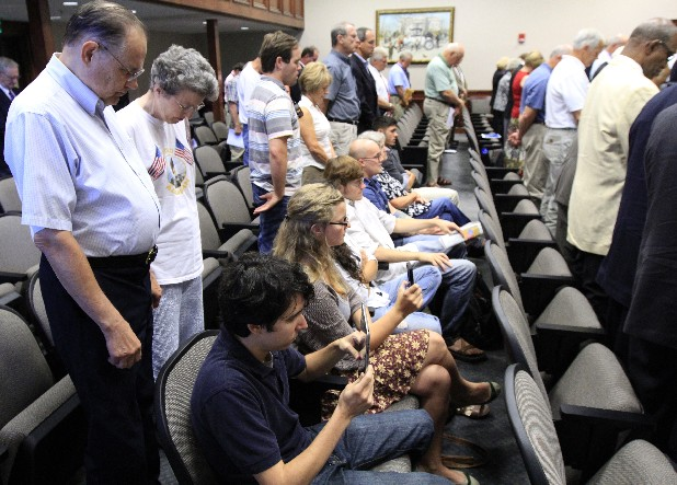 Protesters remain seated during an opening prayer at a Hamilton County Commission meeting in June. The protesters addressed commissioners on their belief that government meetings should open with a moment of silence  instead of prayer.