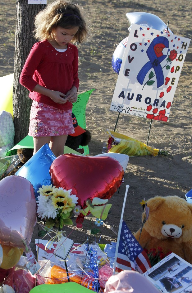 "Serenity Brydon, 7, from Aurora, looks at a memorial near the the Century 16 movie theater Sunday, July 22, 2012, in Aurora, Colo. Twelve people were killed and dozens were injured in a shooting attack early Friday at the packed theater during a showing of the Batman movie, ""The Dark Knight Rises."" Police have identified the suspected shooter as James Holmes, 24."