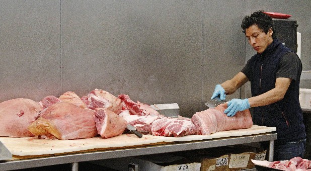 Butcher Freddie Quina cuts meat at Super Cao Nguyen in Oklahoma City. The record drought gripping half the country will help push food prices up by 3 percent to 4 percent next year, the U.S. Department of Agriculture said.
