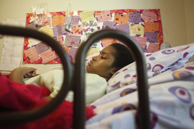 Keoshia Ford, 14, lies in bed below a board covered with well-wishing cards and letters from friends in this file photo.