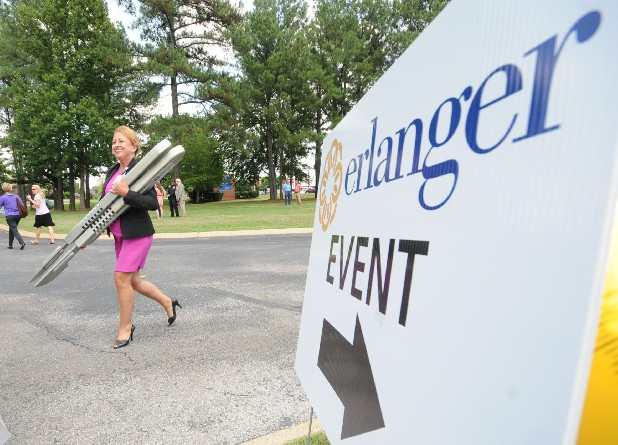 Erlanger East administrator Theresa Radeker carries two oversized scalpels used for breaking ground on a new Emergency Department following a ceremony Wednesday at the Gunbarrel Road Erlanger facility.