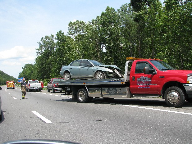 A mangled car is loaded for transport Sunday on Interstate 75 in McMinn