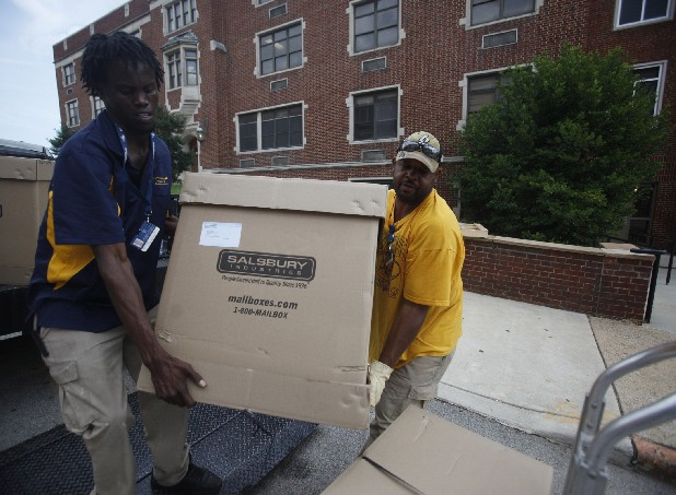Ernest Broderick, left, and Andre Yates, both employees of UTC's housing department, move boxes of mailboxes off a truck in front of the Stagmaier building Wednesday. The University of Tennessee at Chattanooga is prepping dorm rooms for the return of students to the campus.