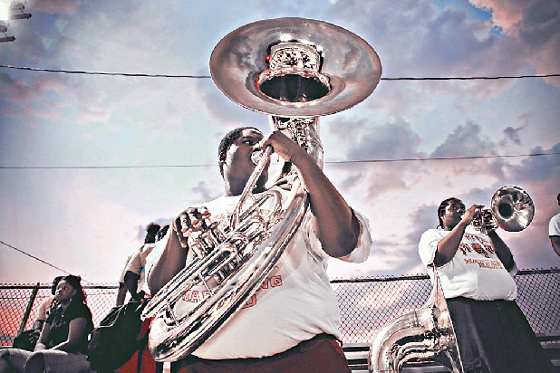 A member of the Howard School marching band plays the sousaphone at a fall home football game.