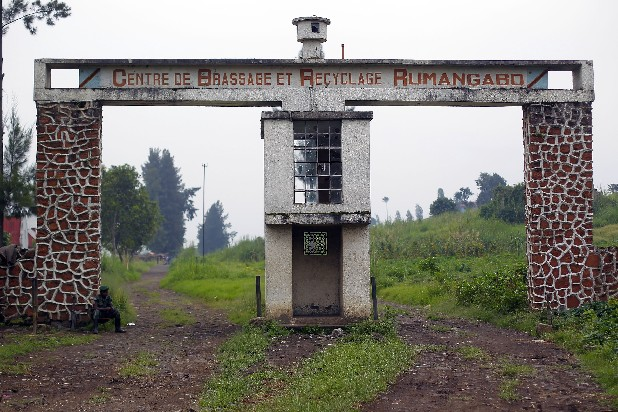 "An M23 rebel sits on a chair at the entrance of eastern Congo's largest military camp in Rumangabo, som 25 miles north of Goma, Thursday Aug. 9, 2012. The camp, formally held by FARDC (the Forces Armees de la Republic Democratique du Congo) government troops, fell to M23 rebels late July. Most know that Congo's 150000-man army is hard done by, poorly and infrequently paid, badly provisioned and ill equipped on the armament front. What they left behind in the base shows they have no incentive to fight. The abandoned camp was home to at least 1000 government soldiers. The base was built by colonial Belgium. The sign on the wall reads: ""Integration and Retraining Center, Rumangabo"""