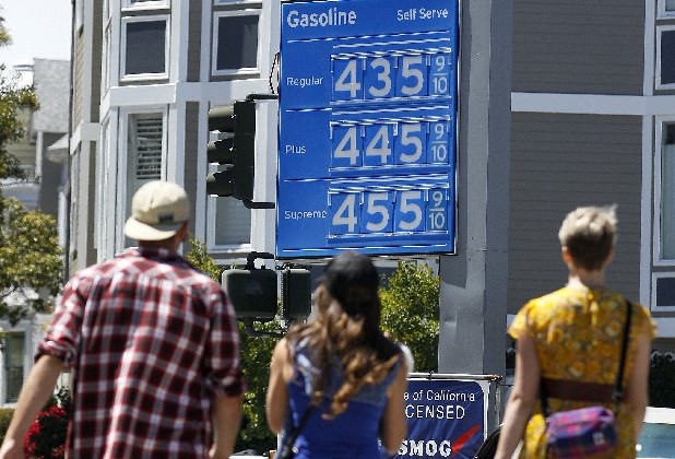 A group of pedestrians walk toward a Chevron gas station price board in San Francisco, Friday, Aug. 10, 2012. Analysts expect West Coast gas prices to surpass $4 a gallon after a fire knocked out a key section of one of the nation's largest oil refineries.