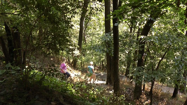 In this Aug. 1, 2012 photo, two women walk from the town of Harpers Ferry, W.Va., onto the Appalachian Trail. Like the people who hike it, the Appalachian Trail is always moving. Technically, Tuesday marks the 75th anniversary of its completion. But the 2,180-mile path stretching across 14 states from Springer Mountain, Ga., to Katahdin, Maine, is never really finished.