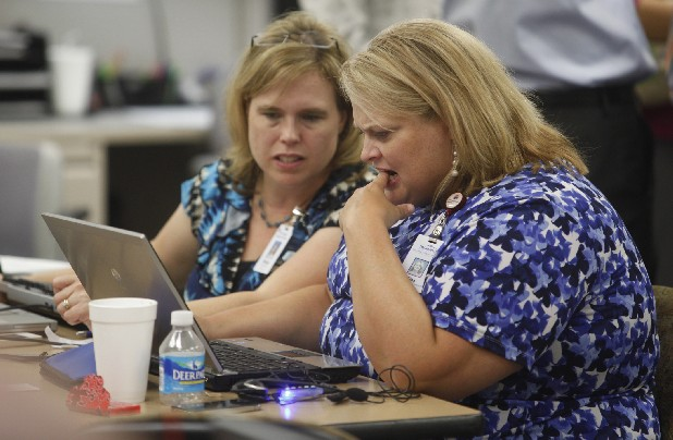 Tina Corbitt, right, and Shelda Truelove try to navigate a new computer system at Parkridge Medical Center on Tuesday. The staff of Parkridge is undergoing a switch from traditional paperwork to electronic forms.