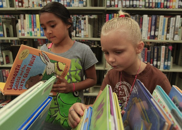 Mia Vanderpool, 7, left, and Brianna Tolbert, 5, look for books to check out during the Dade County Public Library grand re-opening ceremony in 2012 in Trenton, Ga.