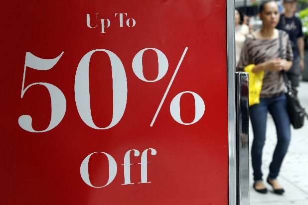 In this July 19, 2012 photo, a shopper in New York passes a sign for discounted clothing. U.S. retail sales rose in July by the largest amount in five months, buoyed by more spending on autos, furniture and clothing. Retail sales rose 0.8 percent in July from June, the Commerce Department reported Tuesday, Aug. 14, 2012. The increased followed three months of declines, including a 0.7 percent drop in sales in June.