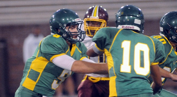 Rhea County quarterback (9) gives to running back (10) as Tyner's (27) eyes the tackle.