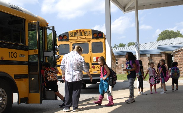 Pamela Lanier, who teaches second grade, directs students onto a bus at East Brainerd Elementary School on Wednesday afternoon.