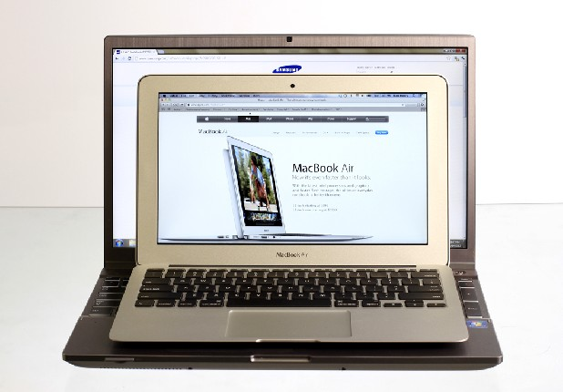 "An Apple 11"" Macbook Air sits atop a Samsung Series 7 15.6"" laptop computer."