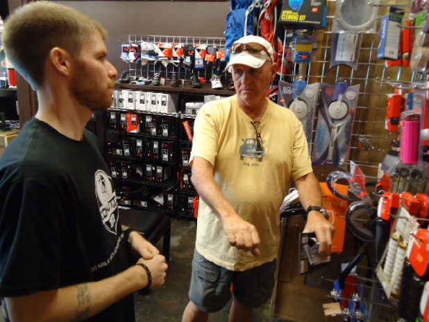 Andrew Barnett, left, a mechanic at Trailhead Bicycle Co., talks with cyclist Jim Harner about biking gloves.