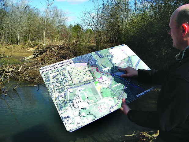 Daniel Carter compares one of many maps produced through the Marion    County Chamber of Commerce and the city of Jasper, showing one of the  locations for greenway walking trails that could become part of a bigger network.  The beaver dam in the center of the photo would be a spot for school students  to watch from a planned observation deck.