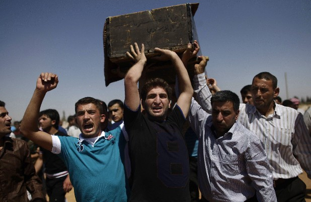 Relatives and mourners carry the coffin of Free Syrian Army fighter Emad Nimeh, 18, who was killed today in an airstrike, during his funeral procession in Al-Bab, on the outskirts of Aleppo, Syria, Friday, Aug. 24, 2012.