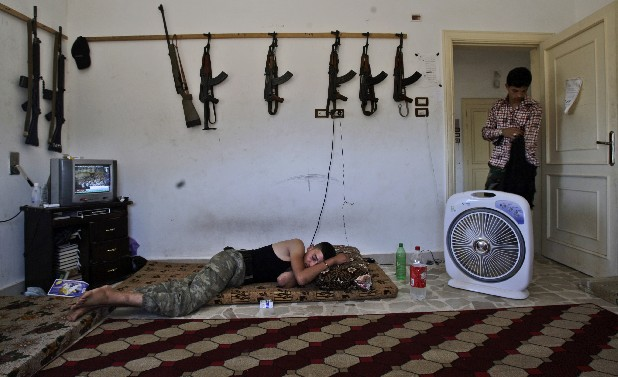 A Syrian rebel, sleeps after returning back from fighting against Syrian army forces in Aleppo, at a rebel headquarters in Marea on the outskirts of Aleppo city, Syria, Sunday, Aug. 26, 2012.