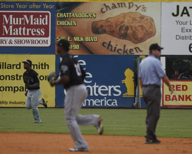 Players and an umpire head for positions between innings during the Lookouts game Tuesday at AT&T Field. The ad for Champy's chicken is stirring interest after it was revealed that the tattoo is actually on the buttocks of the man who supplied the photo.
