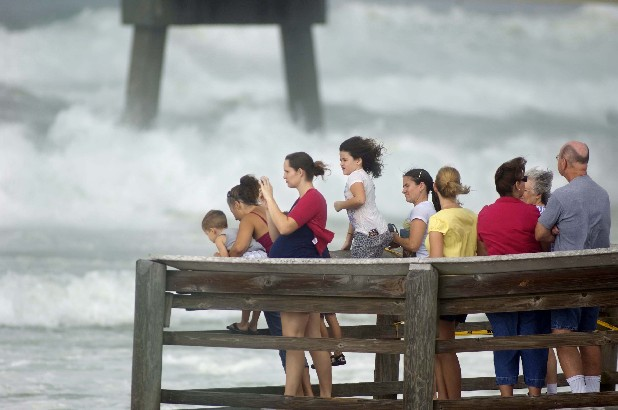 A crowd gathers on the end of the boardwalk on Okaloosa Island in Fort Walton Beach, Fla., Tuesday, Aug. 28, 2012 to watch rough surf generated by Hurricane Isaac as it moves through the Gulf of Mexico with an expected landfall in Louisiana.