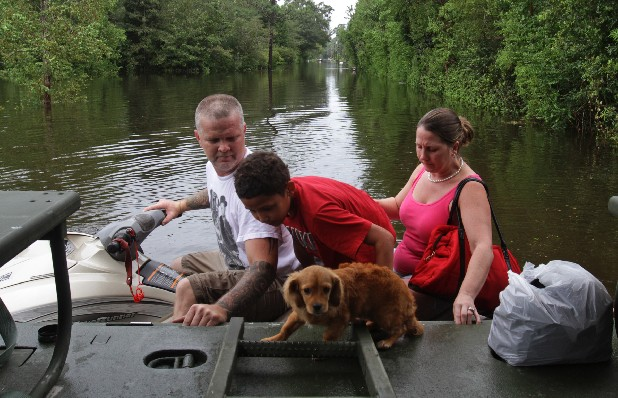 Jeff Delaughter, left, uses a personal water craft to deliver Sabastien Ward, 10, his dog, Stewie, and mother, Winter, to an Army National Guard truck in the Helena community in Jackson County, Miss. on Friday Aug. 31, 2012 after rain from Hurricane Isaac caused flooding in the area.(AP Photo/Sun Herald, John Fitzhugh)