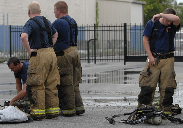 A Chattanooga firefighter wipes his head after responding to a fire inside a warehouse on East 12th Street on August 28.