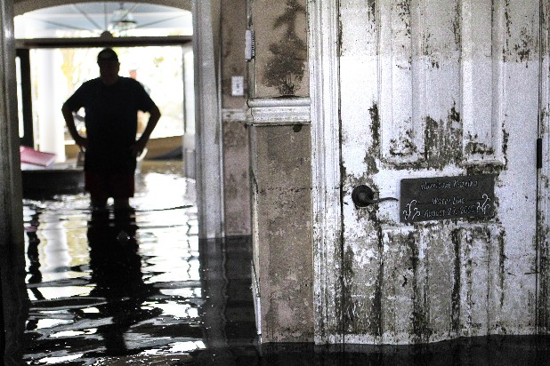 Don Duplantier walks through his flooded home as water recedes from Hurricane Isaac in Braithwaite, La., Sunday, Sept. 2, 2012. In the foreground is a sign marking the waterline from Hurricane Katrina, but floodwater from Isaac went all the way up to the second floor