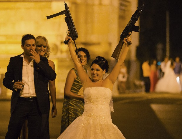 "In this photo shot under iodine street lighting, a Romanian bride poses for pictures at the Arch of Triumph in Bucharest, Romania, after being ""kidnapped"" on her wedding night Sunday, Aug. 26, 2012. It's one of Romania's more colorful customs: bride-napping. And the tradition of snatching the bride from under the nose of groom and guests with the wedding party in full swing is getting bigger, brasher and an increasingly common sight in the Romanian capital, the Balkans' undisputed party town."