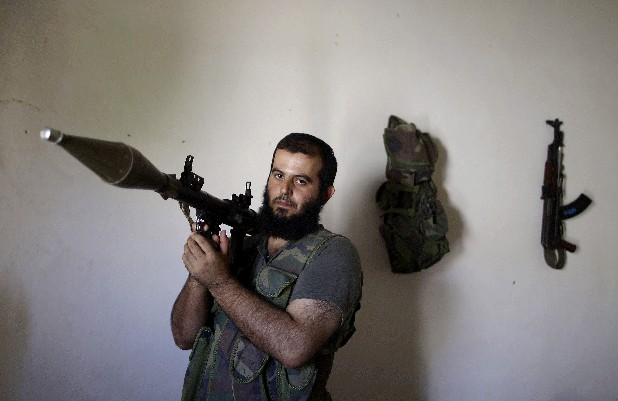 In this Tuesday, Sept. 4, 2012, photo, Syrian rebel fighter, Abu Muslim, 30, a former librarian, poses for a picture at a house where he and others wait their turn to go and fight against government forces in Aleppo, in Marea on the outskirts of Aleppo city, Syria. Syria's rebels have turned to a new tactic of attacking bases, trying to stop the jets and attack helicopters that have wreaked devastation on their fighters and civilians in the battleground city of Aleppo and the nearby countryside. Abu Muslim became a specialist in rocket-propelled grenades during his military service a decade ago. He said in the tight confines of urban warfare, taking out the regime's older tanks, wasn't a problem.