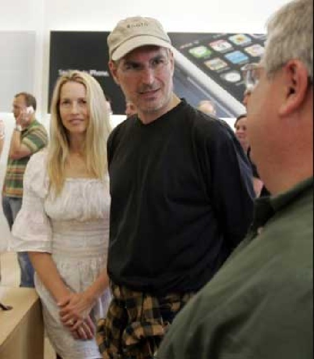 File photo from June 29, 2007, Laurene Powell Jobs and her husband, Apple co-founder and chief executive Steve Jobs, met with customers after the launch of the iPhone in Palo Alto, Calif. Laurene Powell Jobs is a philanthropist and president and co-founder of College Track, an after-school program that helps under-served students work toward a college degree. She also sits on the board of many organizations, including Teach for America's. Jobs currently serves on the White House Council for Community Solutions. (Paul Sakuma / AP)