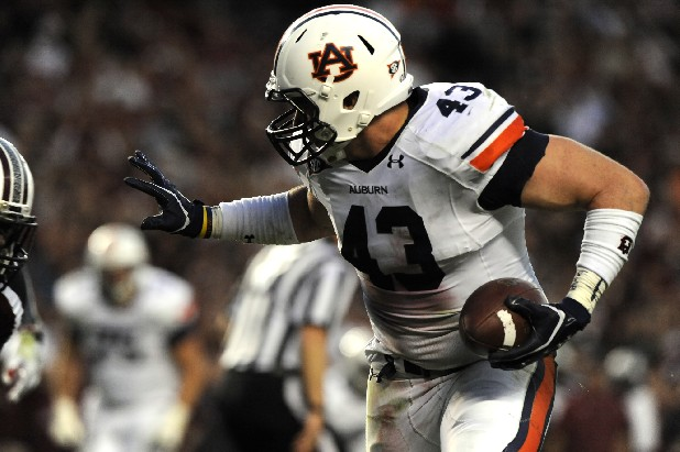 Philip Lutzenkichen scores a touchdown for Auburn in this file photo.
