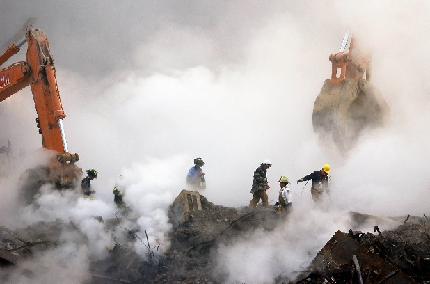 In this Oct. 11, 2001 file photo, firefighters make their way over the ruins and through clouds of smoke at the World Trade Center in New York.  Many of the first responders and those who labored at the site in the months following the attacks suffer from a variety of respiratory ailments after working at the World Trade Center site. Nearly two years after President Obama signed the James Zadroga 9/11 Health and Compensation Act into law, about 60,000 responders and survivors continue to receive monitoring and treatment for their illnesses as part of the World Trade Center Health Program, one of the lawís two components.