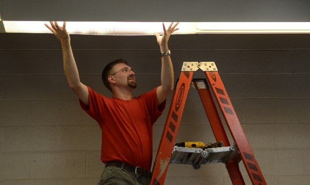 Michael Bratcher installs new lighting at the Sheila Jennings Westside Community Center Thursday during the United Way's national day of caring.