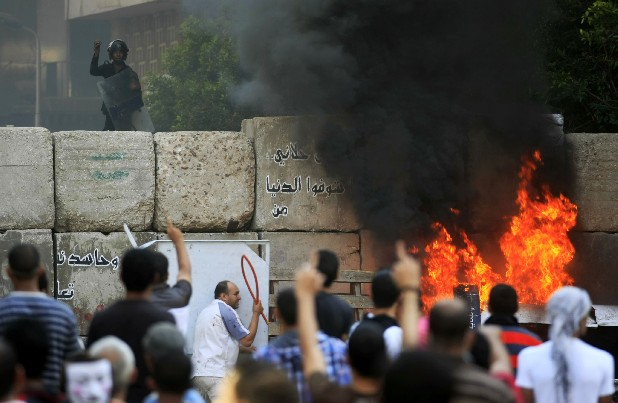 Egyptian protesters clash with security forces near the U.S. Embassy in Cairo, Egypt, on Friday.