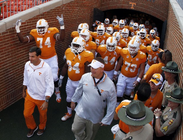 Tennessee head coach Derek Dooley, bottom left, leads his team onto the field before the start of an NCAA college football game against Florida on Saturday, Sept. 15, 2012, in Knoxville, Tenn.