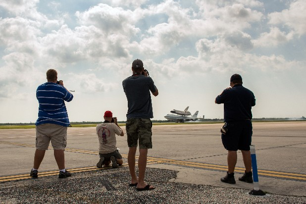 Spectators take photos of the space shuttle Endeavour, carried atop NASA's 747 Shuttle Carrier Aircraft, as it lands at Ellington Airport on Wednesday, Sept. 19, 2012, in Houston. Endeavour stopped in Houston on its way from the Kennedy Space Center to the California Science Center in Los Angeles, where it will be placed on permanent display. (AP Photo/Houston Chronicle, Smiley N. Pool, Pool)