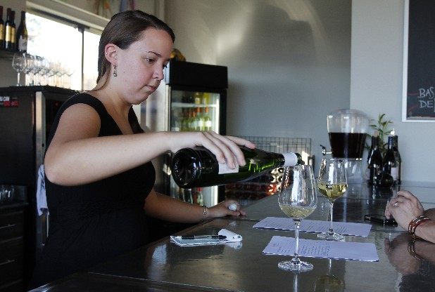 Kathryn Olinger, a server, pours wine for customers inside Brix Nouveau, a new wine bar on the NorthShore that also offers coffee and cheese and meat plates.