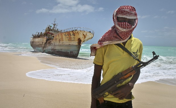 In this photo taken Sunday, Sept. 23, 2012, masked Somali pirate Hassan stands near a Taiwanese fishing vessel that washed up on shore after the pirates were paid a ransom and released the crew, in the once-bustling pirate den of Hobyo, Somalia. The empty whisky bottles and overturned, sand-filled skiffs that litter this shoreline are signs that the heyday of Somali piracy may be over - most of the prostitutes are gone, the luxury cars repossessed, and pirates talk more about catching lobsters than seizing cargo ships.