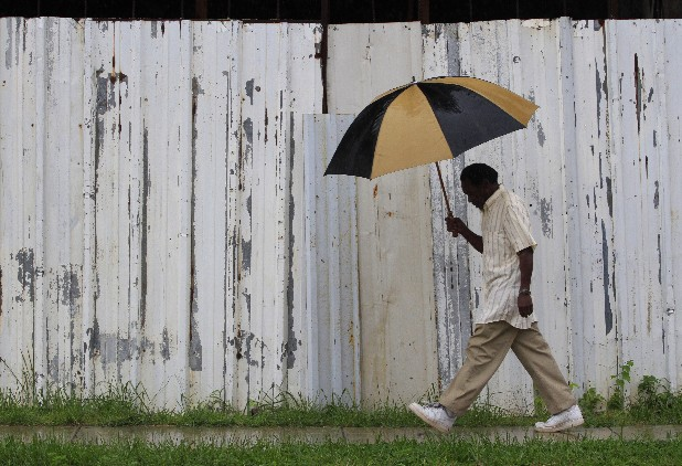 Lloyd McCoy braves the rain to make his daily walk past a boarded-up building off Main Street in Chattanooga early Monday morning.