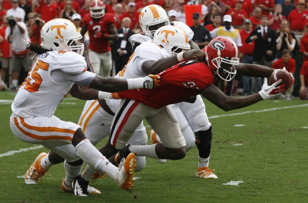 Georgia flanker Tavarres King reaches for extra yards as Tennessee linebacker A.J. Johnson tries to pull him back Saturday at Samford Stadium in Athens, Ga.